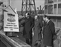 Marshall Aid sugar is unloaded at London's Royal Victoria Dock, February 1947, watched by US and UK officials