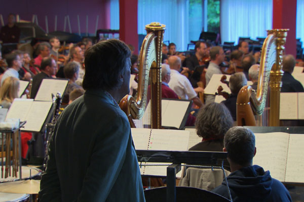Stephen Fry watches the orchestra rehearse for the Bayreuth Festival