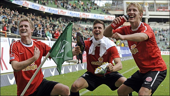 Mainz's Andre Schuerrle, Adam Szalai and Lewis Holtby celebrate with the corner flag after beating Werder Bremen