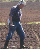 a metal detectorist scanning a field with his detector