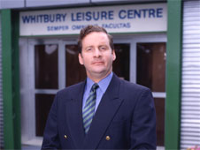 A still from the sitcom 'The Brittas Empire'. Leisure centre manager Gordon Brittas stands outside Whitby New Town Leisure Centre