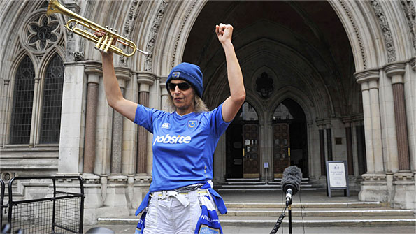 A Portsmouth fan celebrates outside the High Court