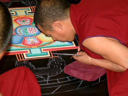 Monks, dressed in red tunics with close-cropped hair, lean over a circular design marked out in chalk on a black tabletop.  Their faces are inches from the surface.  Resting their hands on small cushions, they are pouring coloured sand through small metal tubes into the spaces marked by the chalk outline