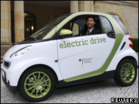 Germany's Economy Minister Philipp Roesler poses in an electric car
