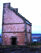 16th-century Scottish building with pink walls and sharply sloping roof