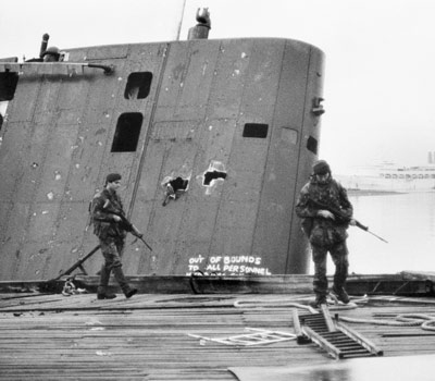 Royal Marine patrol passing the submerged fin of the Sante Fe at South Georgia