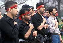 Muslim men wearing red headbands in the Ashura procession