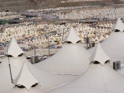 Large area of land covered with white topped marquee tents for miles