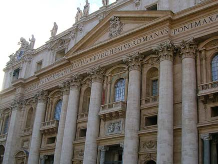 Facade of Saint Peter's Basilica, framed by pillars with Latin legend over the doors