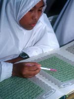 A girl wearing a headscarf reads the Qur'an
