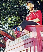 Kid Acne sat on a telephone box