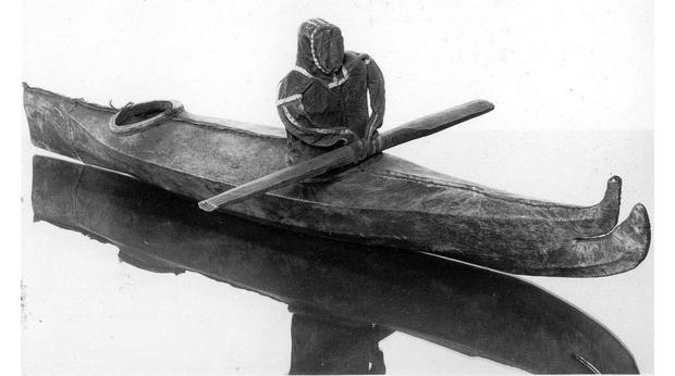 Model kayak with doll holding paddle
