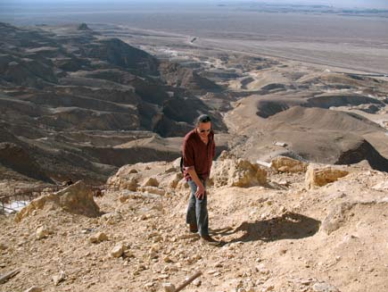 Nicholas Buxton climbs a long, winding rocky path with the Egyptian desert and mountains stretching out below and behind him