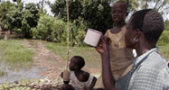 A woman and two kids drinking water from a river in Kenya