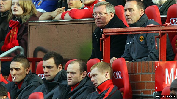 Wayne Rooney sits on the Old Trafford bench as Sir AlexFerguson watches ther action