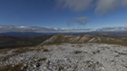 View from the rocky top of Beinn Iutharn Mhor towards other mountains on a clear, sunny day.