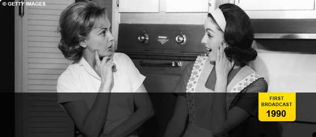 Two 1950s housewives chat in the kitchen.