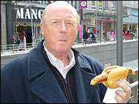 BBC Radio Manchester commentator Fred Eyre samples a bratwurst in Hamburg