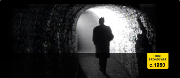 Silhouette of a man walking through a tunnel.