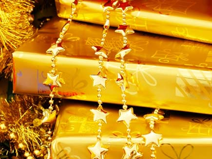 Presents wrapped in luxurious gold wrapping paper, draped with golden bead chains
