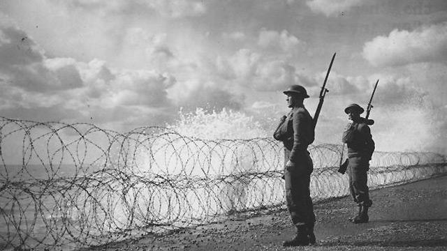 Armed soldiers stand guard on a south coast beach, 2 September 1940.
