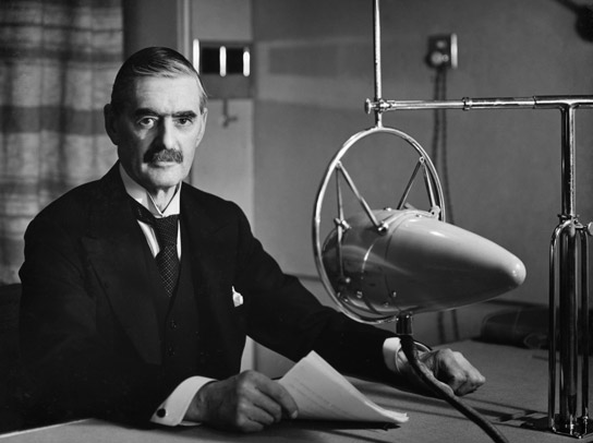 A photograph of the Rt Hon Neville Chamberlain MP at a BBC microphone.