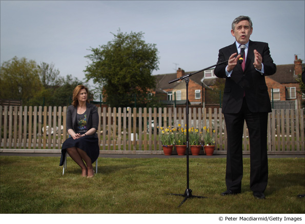 Gordon Brown is watched by his wife Sarah Brown as he speaks to supporters in the garden of Arnold Mill Primary School