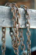 Chains hanging over wooden fence