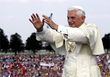 Pope Benedict XVI in front of crowds of young Catholics with hands held out in blessing