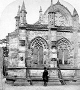 Black-and-white photograph of a man standing under the wall of Rosslyn Chapel