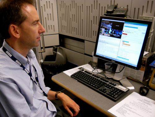 John Fletcher is pictured sitting at a computer terminal, using the Ingex software to manage the ingest of video and audio content during a recording of The Bottom Line