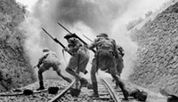 Bayonet-fixed rifles held firmly, members of the British 8th Army are pictured heading into the smoke of battle as they rush a Sicilian railway strongpoint