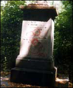 Tomb with red graffiti on it.