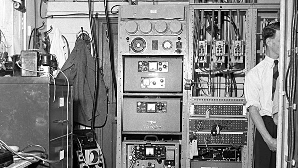 Black and white photo of office with cabinets of 1950s electronics
