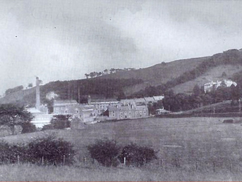 Black and white view of Atheenic Mill buildings and chimney stack, set on a largely grassy slope. There are two short terraces of houses by the mill buildings and a large detached house higher uphill.