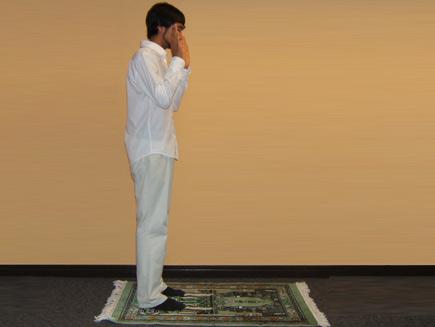 A man stands with his hands raised to his ears on a prayer mat