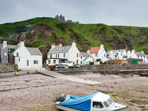 Colour view showing one small motorboat pulled up onto the shore, with a row of cottages beneath tall cliffs behind.