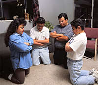Four Mormons kneel in prayer