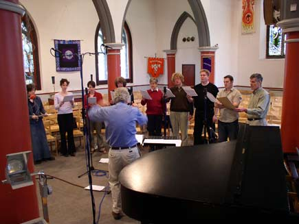 Nigel Swinford conducting nine choir members, grouped in a small floorspace in the middle of the church.  Around them are chairs, microphone stands, an overhead projector and a piano