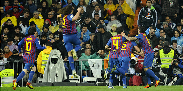 Barcelona's players celebrate after Real Madrid's Brazilian defender Marcelo scored an own goal during the 'El clasico' Spanish League football match Real Madrid against Barcelona at the Santiago Bernabeu stadium in Madrid on December 10, 2011