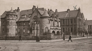 Black and white view of two-storey hospital building featuring a range of pitched-roofed main blocks with turrets. The hospital stands at the crossroads of two wide streets along which run a number of tram tracks.