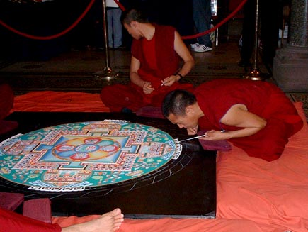 Monks seated around the mandala, now working on the beginnings of the outer border