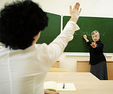 A teenage boy putting up his hand to answer a question in a French lesson.