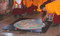 A monk has brushed away a quarter of the mandala into heaps of grey sand