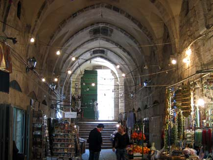 Market stalls are set up in a covered alleyway with a high, arched ceiling.  An arched doorway in the background lets some light in, and electric lights are strung across the alley