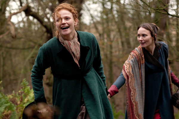 Anne Lister, played by Maxine Peake, and Marianna, played by Anna Madeley, run hand in hand through the woods