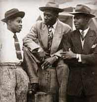 John Hazel, Harold Wilmot and John Richards aboard the Windrush, Tilbury 1948. The men are dressed in suits and hats.