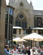 People sitting at cafe tables beneath the façade of Southwark Cathedral