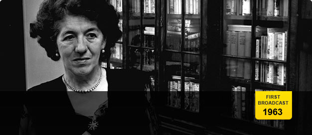 Enid Blyton photographed in 1952, standing by her bookcase in Green Hedges.