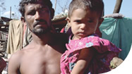 Bangladesh - man holding child in front of home destroyed by Cyclone Sidr